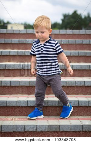 Two years old boy walking down on the stairs