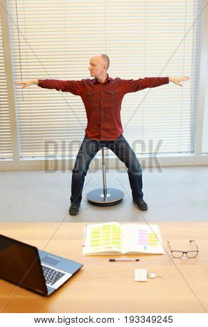 middle age man stretching arms, relaxing neck - short break for exercise on pneumatic stool in office