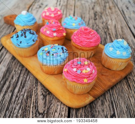 Pink and Blue Cupcakes. Homemade colorfully decorated pink and blue cupcakes on a light wood cutting board with rustic background