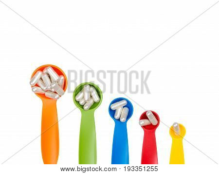 White Capsules Pills On Colorful Measuring Spoon Isolated On White Background. Increase The Dosage O