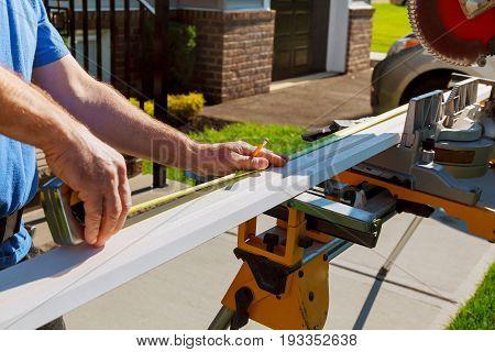 Man Cutting Crown Mouldingon Electric Saw