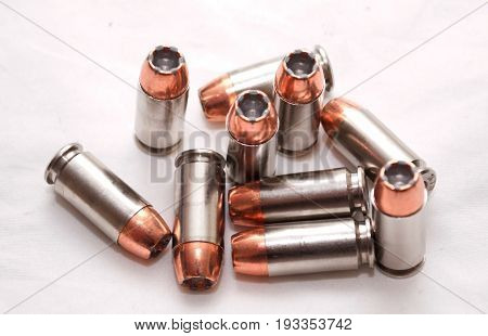 Ten 40 caliber hollow point bullets with a white back ground