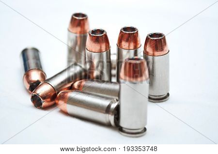 Nine 40 caliber hollow point bullets with a white background