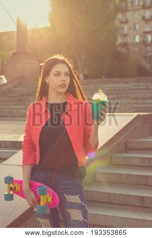 A teenage girl holding a glass with fruit fresh. She has a skateboard. Active way of life in urban space. Youth fashion.