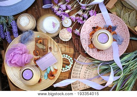 Flat lay spa accessories, handmade artisan soap, fresh flowers, wisp of bast, candles, bath salt etc. Wooden backdrop