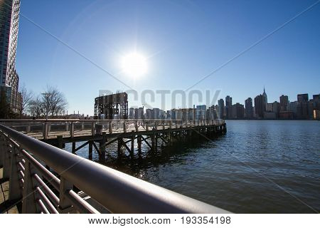 iconic gantries of Gantry State Park and fence of pier opposite city with blue sky, New York