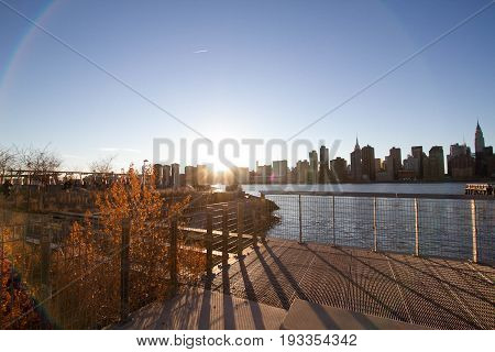 Plants and walkway near to East river and Manhattan at Gantry Plaza State Park with sunset and lens flare