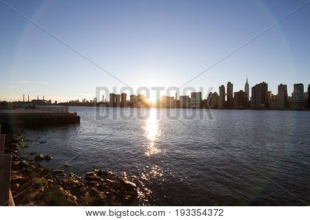 Sunset behind Manhattan reflects on East river