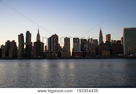 Empire State Building and buildings under the shade in Manhattan with East river, New York