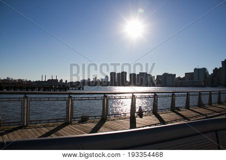 Fence and wooden walkway next to East river at Gantry Plaza State Park with blue sky