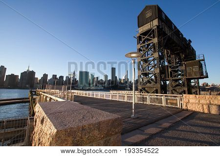 Transfer bridges, support gantries, and piers at Gantry Plaza State Park And buildings in Manhattan before sunset