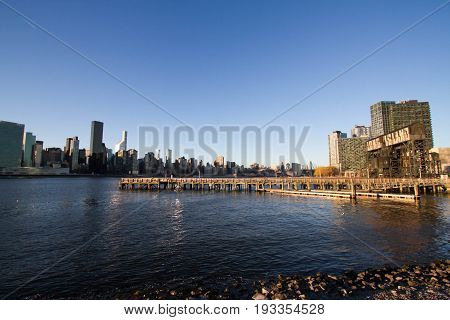 Pier on East river at Gantry Plaza State Park and buildings in Manhattan before sunset