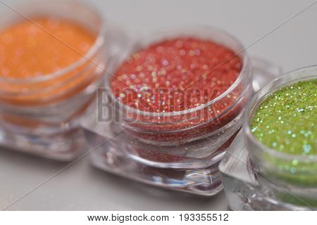 Closeup set of colorful nail makeup glitter in round jar isolated on white background. Concept of beauty and makeup