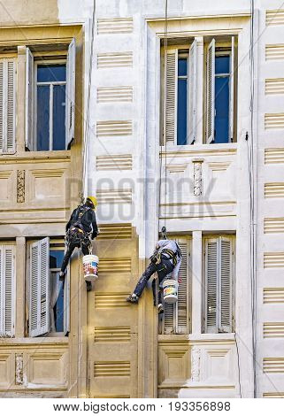 MONTEVIDEO, URUGUAY, JUNE - 2017 - Two workers hanging by cables painting the facade of apartment building in Montevideo Uruguay