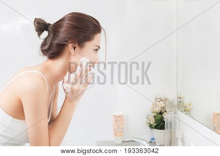 Woman happy cleanses the skin with foam in bathroom. poster