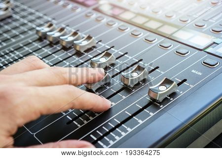 Hand adjusting audio mixer console buttons faders and sliders.