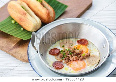 Fried eggs on pan with bread for breakfast.
