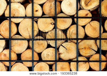 firewood stacked on the woodpile in iron cage background.