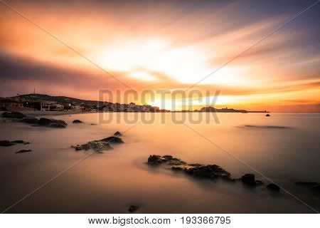 Dramatic long exposure sunset over the beach at L'Ile Rousse in the Balagne region of Corsica with rocks in the foreground bars and restaurants along the front and the red rock port and lighthouse in the distance