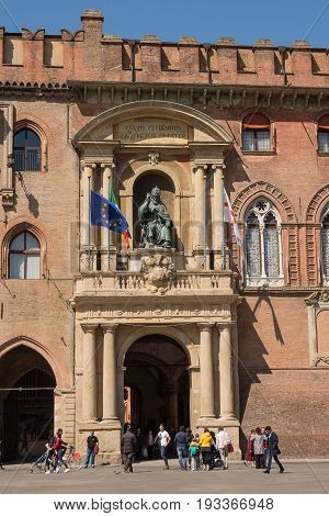 Bologna Italy - April 22 2017: Door of Palace of Accursio in Piazza Maggiore of Bologna with tourists on a sunny day