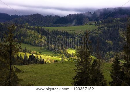 The sunlight makes its way through dense mountain clouds and illuminates the valley in the Carpathian mountains