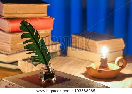 Quill pen, inkwell and old books by candle light