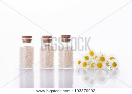 Herbal remedy alternative medicine. Chamomile flowers and homeopathic medication.