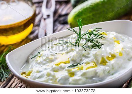 Tzatziki. Traditional greek dip sauce or dressing tzatziki prepared with grated cucumber sour cream yogurt olive oil and fresh dill. Mediterranean cuisine.