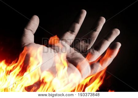 Burning hand on a dark background. conceptual, fright,