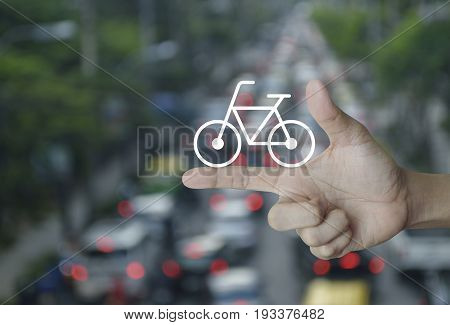 Bicycle flat icon on finger over blur of rush hour with cars and road Healthy lifestyle concept