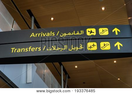 Airport arrival sign and transfer sign -  flight arrival and transfer yellow sign at airport in English and Arabic