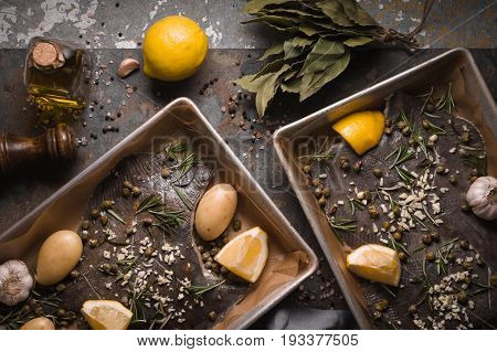 Baking dish with raw flounders and seasoning on the stone background  top view horizontal