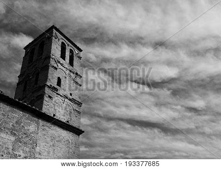 Medieval belfry of the Church of San Giuliano with clouds in the center of the ancient ruined of Faleria a small city near Rome (Black and White)