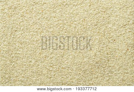 Smooth and even sand surface. Light brown and ocher colored grains of sand. Backgrounds. Closeup macro photo directly from above.