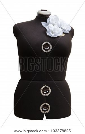 Female lady valet mannequin without head made of a black fabric with adjustable sizes with an ornament from three white artificial plastic roses with leaves on a shoulder on isolated background.