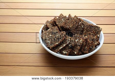 Bowl of Crispbread on a Wooden Background