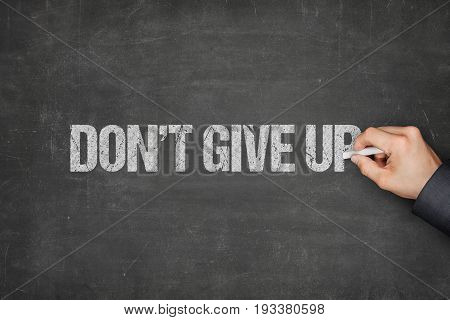 Cropped hand of businessman writing dont give up text on blackboard