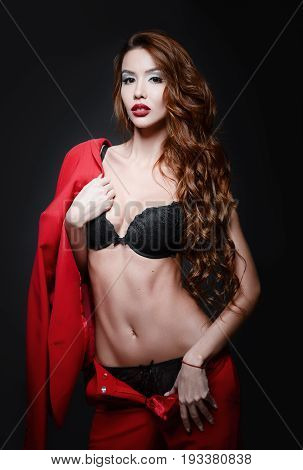 Studio fashion shot: a beautiful sexy young woman in black underwear and red suit