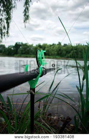 Fishing rod on a fishing pond with a blurred summer day background
