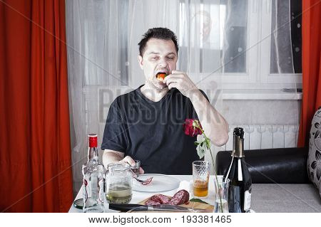Drunk Unshaven Sad Man Sits At A Table With Drinks And Snacks, Holding A Glass And Eat A Sandwich Wi