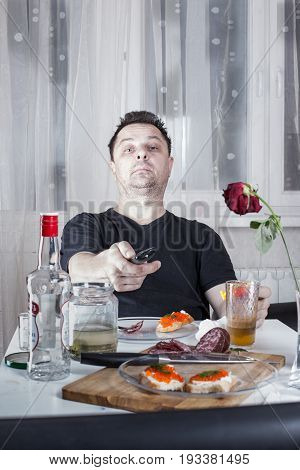 Drunk Unshaven Man Sitting At A Table With Drinks And Snacks, Holding A Remote Control And Looks At