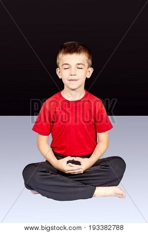 Little boy sitting in meditation pose on the black background