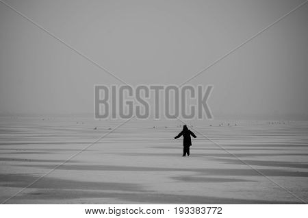 Winter on the lake. Ice skating. Frozen lake. Silhouette of a man ice skating on a frozen lake. Black and white. Fairy tale.