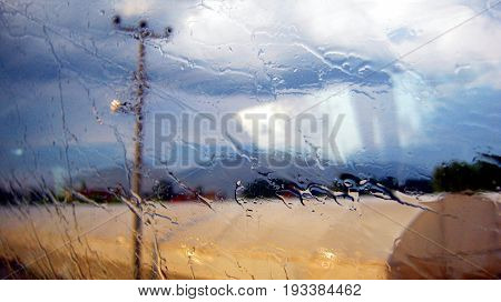Smeared raindrops on side window of coach on the first plane. On the second plane blurred semaphore.