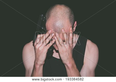Depression. Depressed lonely man with suicidal thoughts holding gun and cover his face. Dark image. Isolated on black background. Suicidal concept.