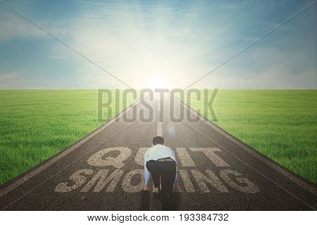 Back view of young businessman ready to run while kneeling on the road with text of quit smoking