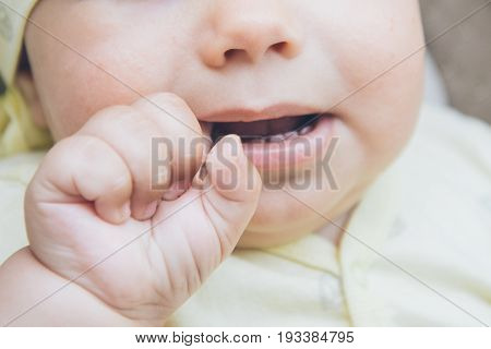 baby suck his finger because of teething close up