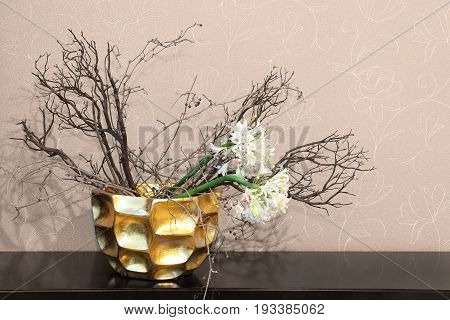 Home decor gold bowl with dry flowers on wooden table