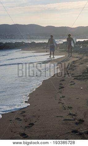PALMA DE MALLORCA BALEARIC ISLANDS SPAIN - JUNE 29 2017: Surfer couple at Molinar beach on a sunny and windy summer evening on June 29 2017 in Palma de Mallorca Balearic islands Spain.