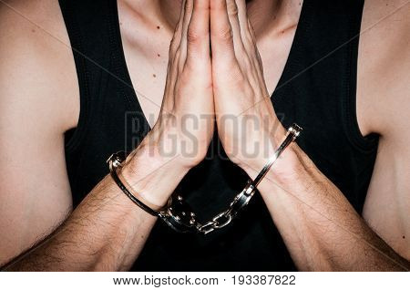 Prayer with handcuffs. Man with handcuffs on his hands pray to God. Crime remorse concept. Dark image.